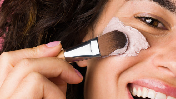 woman applying product onto face with a brush