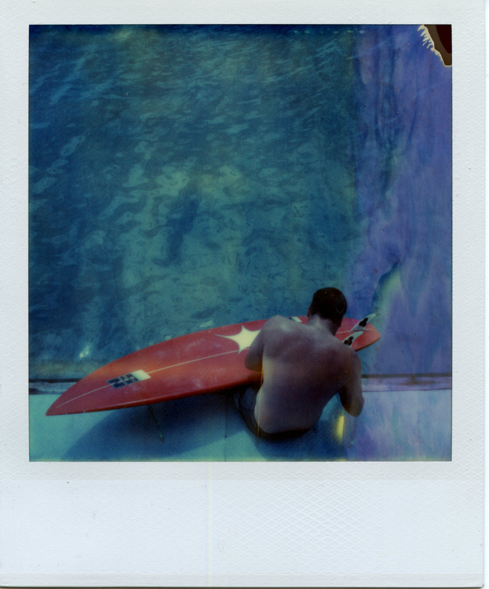 Polaroid image of a surfer repairing a board
