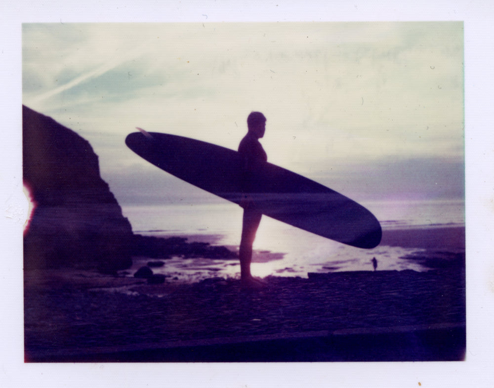 Polaroid image of a Silhouette of a surfer at sunset