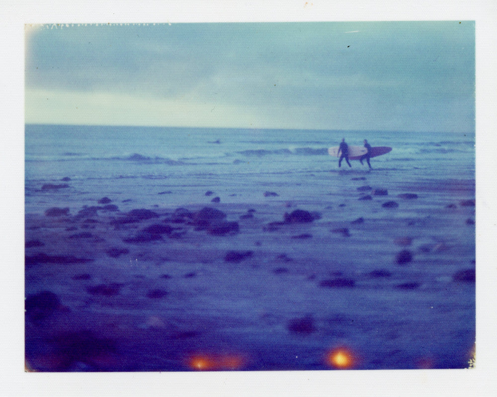 Polaroid of distant longboarders at Porthtowan