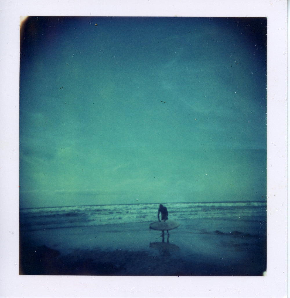 Polaroid image of surfer checking his board
