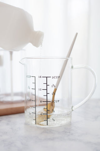 glass measuring cup with aloe, spoon