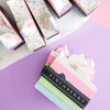 Seven slives of Darling Gourmet Bar Soap on a white, pink and purple background