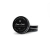 Down to Earth Solid Perfume in black circular tin container with white lettering