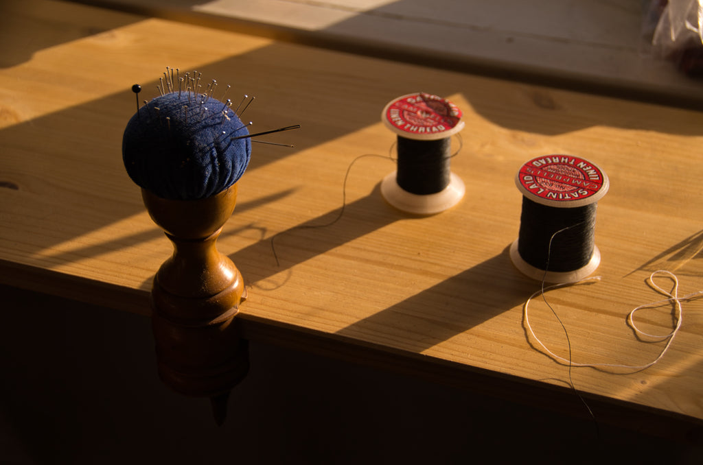Pincushion and sewing threads by the window