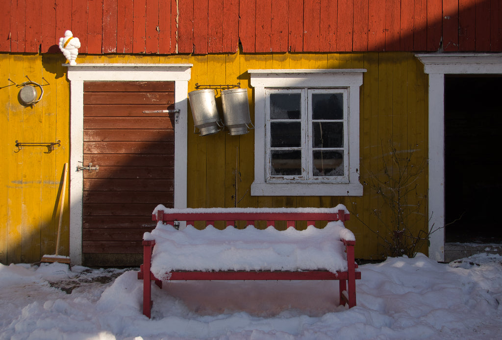 Snow-covered bench by the barn