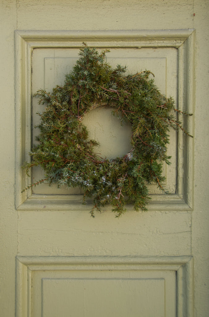 Juniper wreath on green door