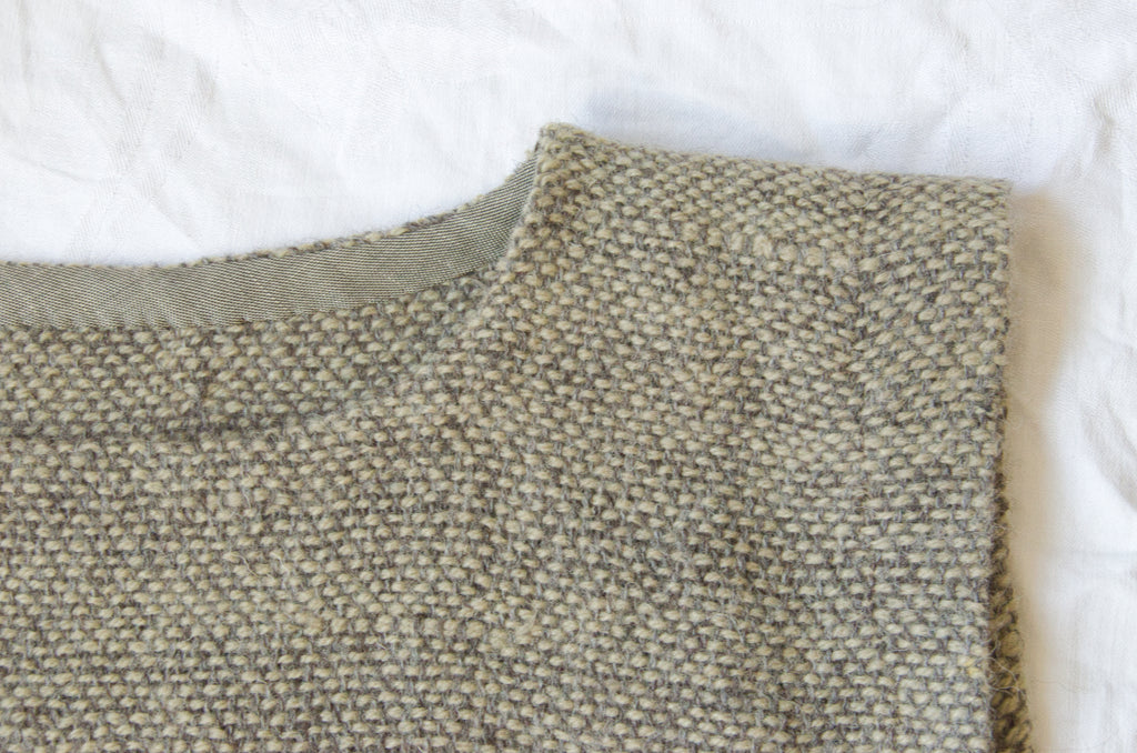 Neckline detail of hand-woven wool dress