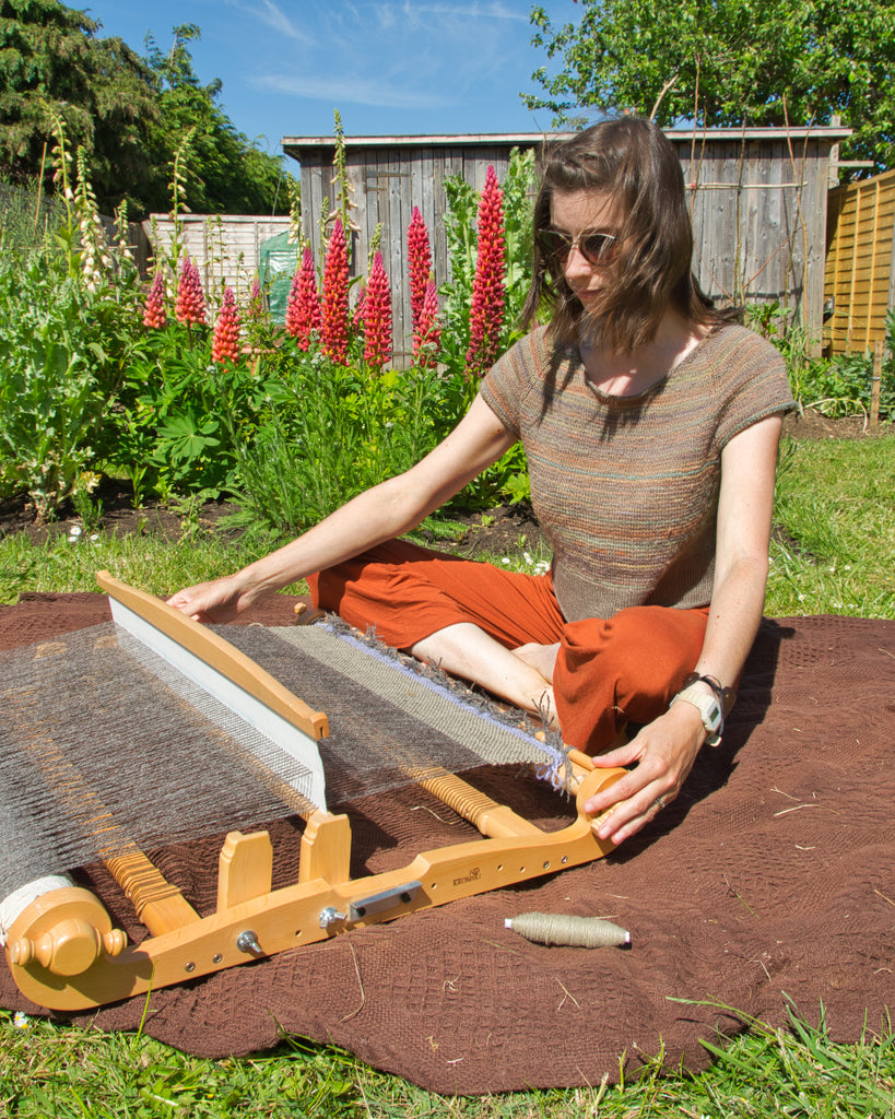 Weaving on a rigid heddle loom in the garden
