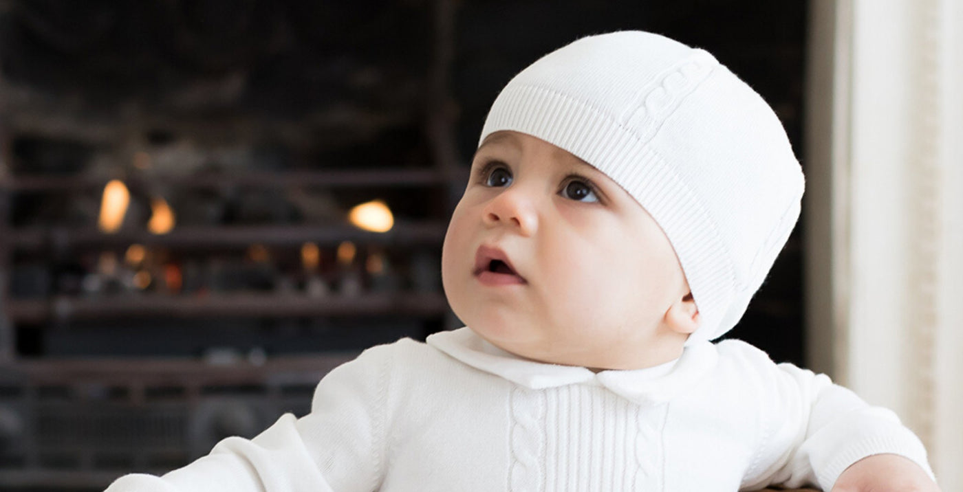 Newborn baby in neutral clothing in front of a cosy fireplace