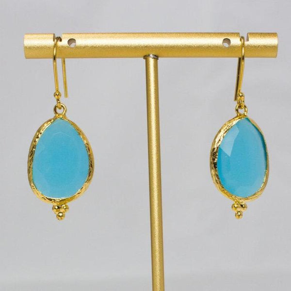 Turquoise stone earrings hanging on a jewellery stand