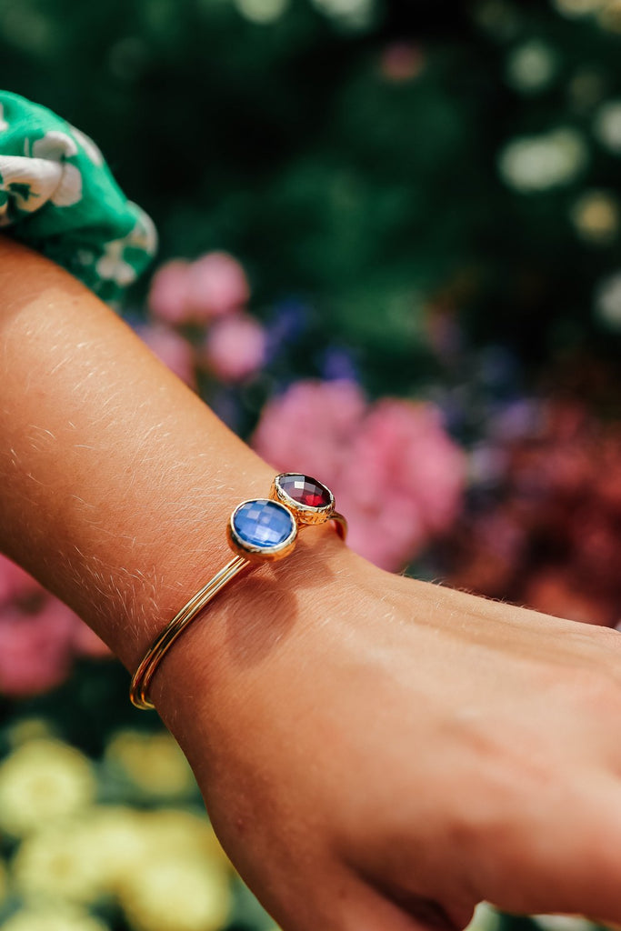 Blue crystal stackable bracelet on a woman hand with pretty garden in the background