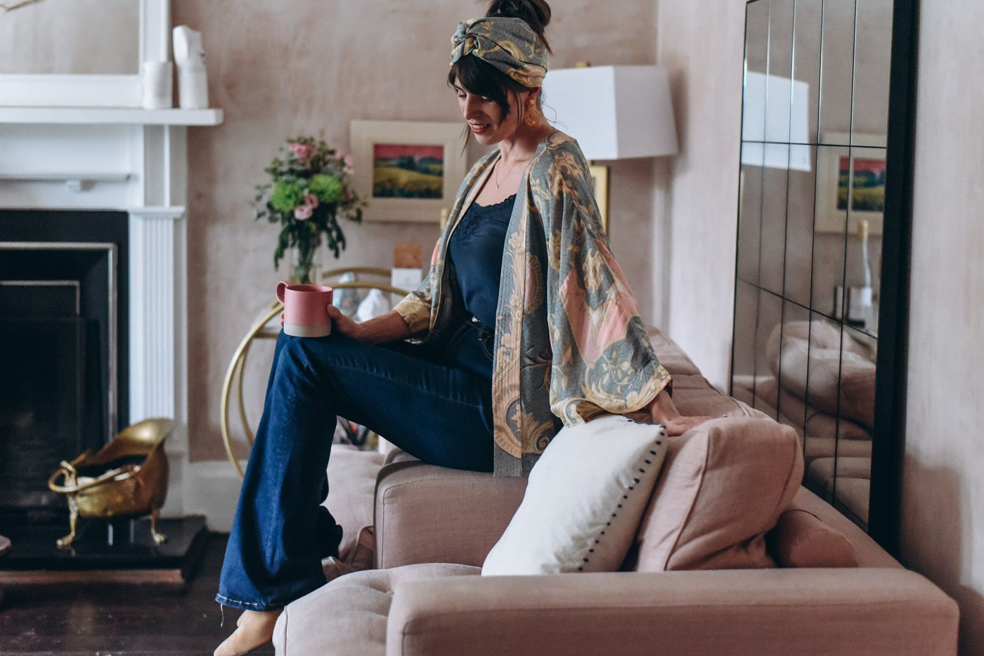 Fashionable woman in boho clothing sat on the sofa with a cup of tea