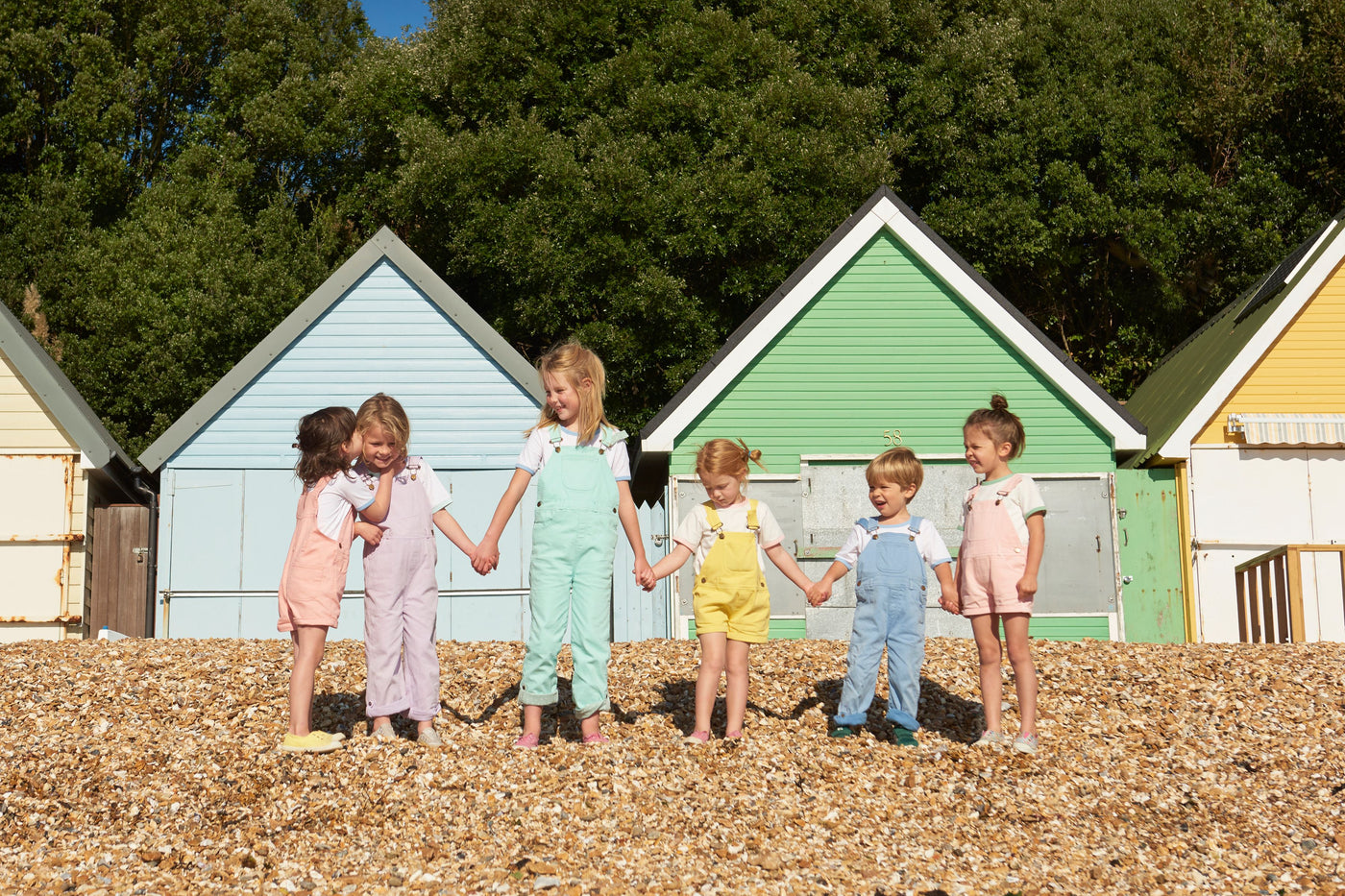 Children in Dotty Dungarees on a beach with colourful beach huts
