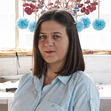 Portrait of Karolina Merska in her studio, with one of her pajaki chandelier creations hanging colourfully behind her.