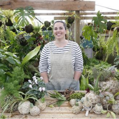 Plant specialist Coraleigh Parker in her shop in New Zealand, surrounded by greenery.