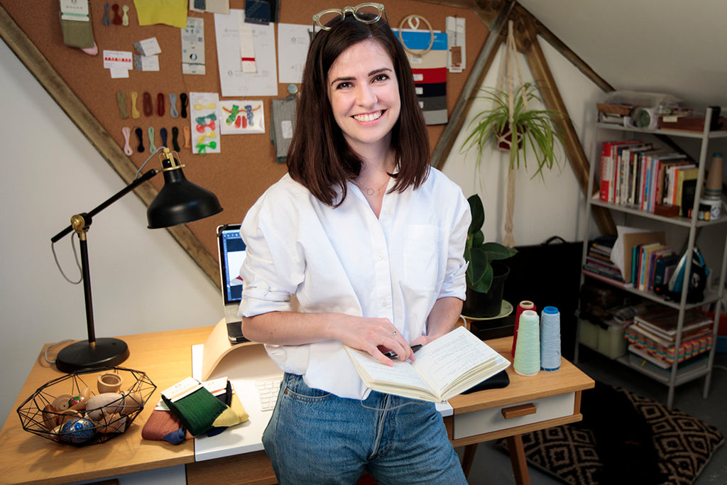 Emma Mathews standing in her office in front of her desk, smiling and holding a book.