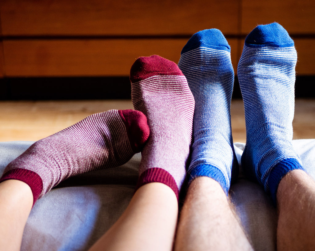 Two pairs of feet wearing Socko socks, one with blue socks and the other with red.