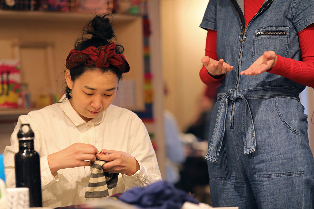 Woman sitting down working on darning, with a figure standing next to her explaining the process.