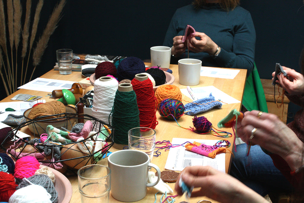 A table filled with darning materials with people sitting around, hands over the table grabbing the materials.