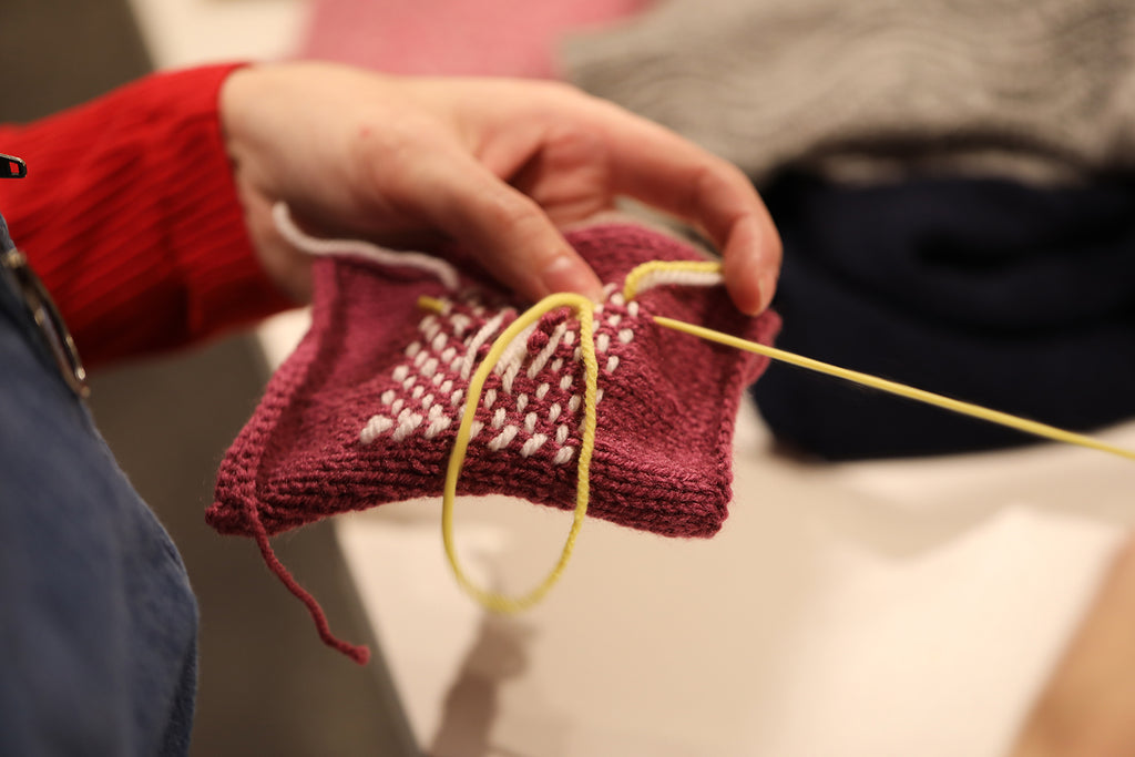 A hand holding a piece of knit textile, being darned.