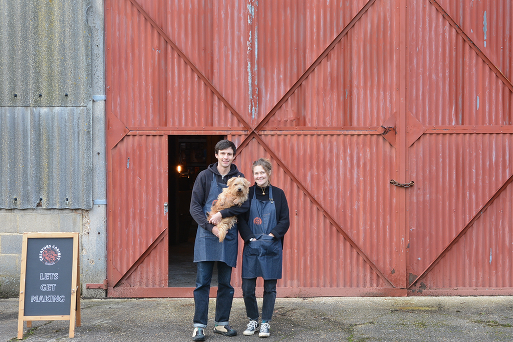 Tom and Ollie standing in front of their barn with their dog Finn