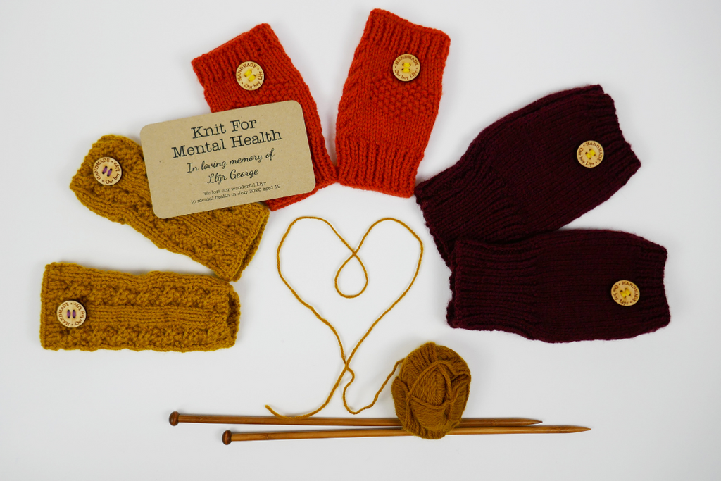 Three pairs of wrist warmers in a semi-circle, surrounding yarn twisted into a heart shape, with the ball of yarn and knitting needles beneath.