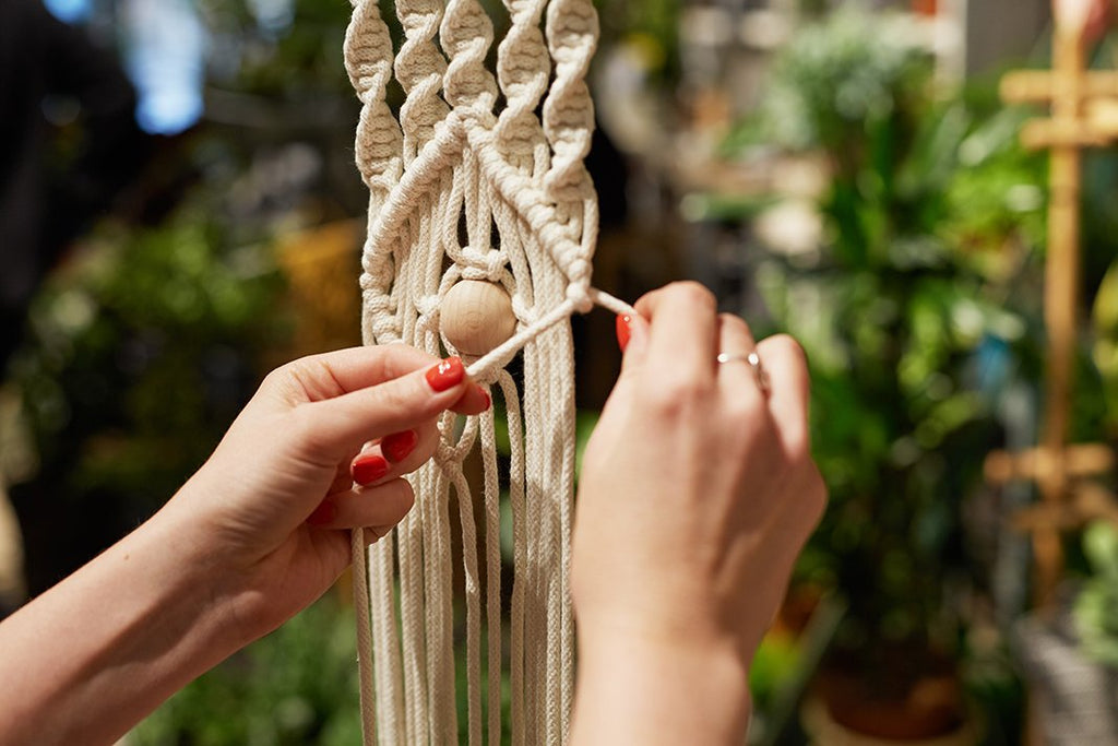 "Make an ""eye-spy"" macrame wall hanging with white natural cotton cord and wooden bead."