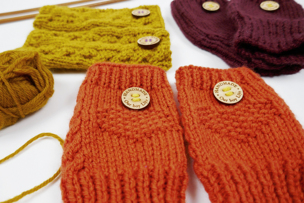 Three pairs of wrist warmers on a white surface with a ball of yarn and knitting needles to the side.