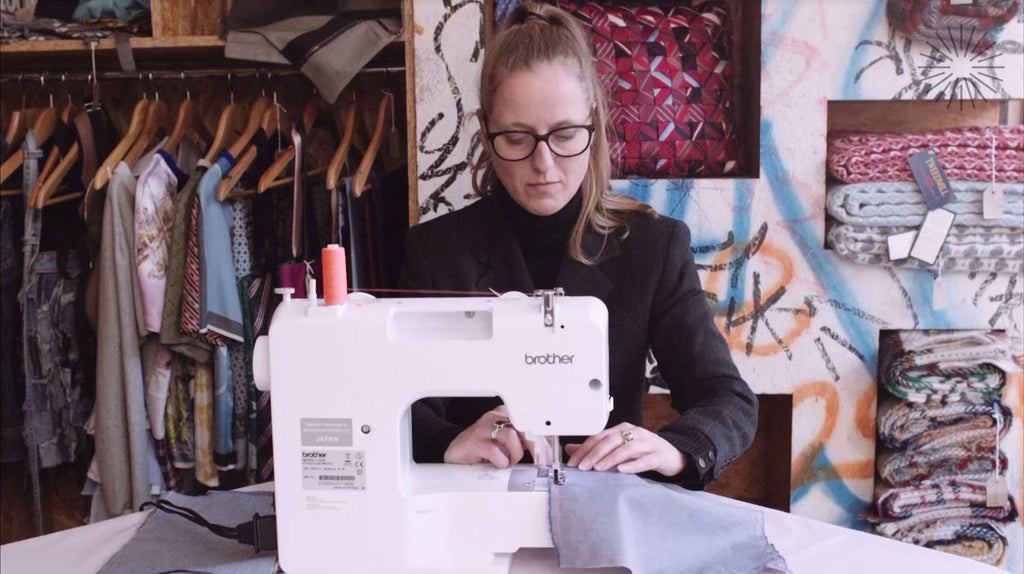 Barley Massey in front of her sewing machine, sewing textiles together