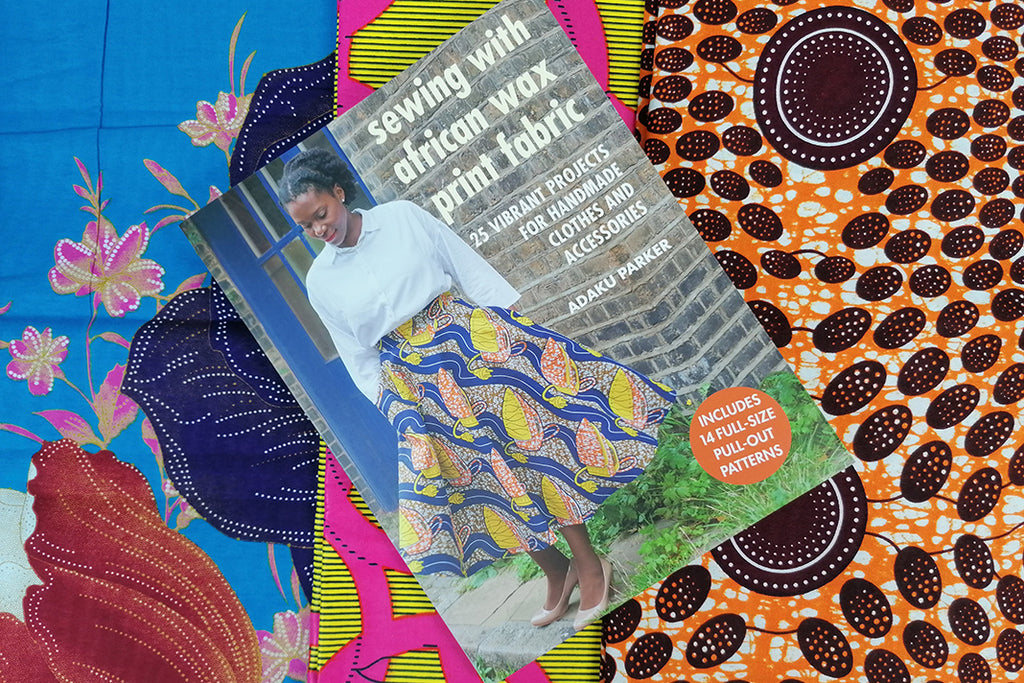 """A book titled """"Sewing with African Wax Print Fabric"""" on a surface of brightly coloured and patterned textiles. On the cover of the book is a woman wearing a flowing colourful dress."""