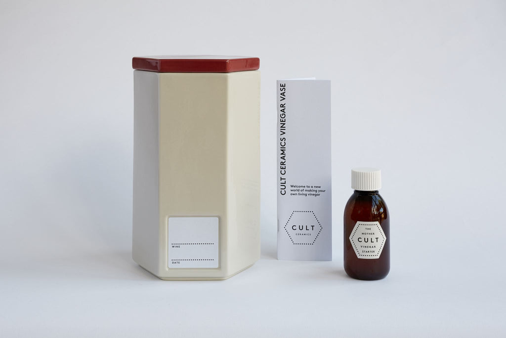 A ceramic white vinegar vase with a red top next to a jar of vinegar starter and booklet.