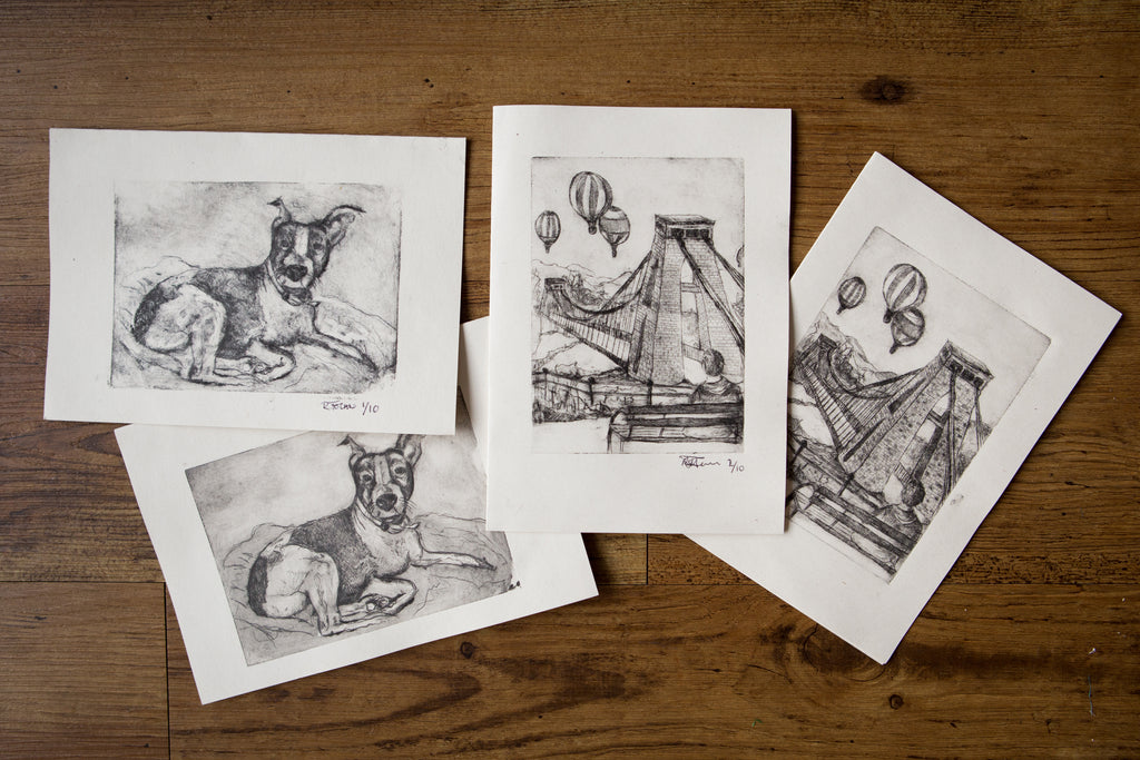 A selection of intaglio drypoint printed cards, featuring a dog and a scenery over a bridge
