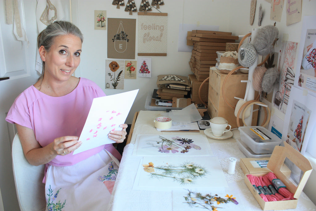 Leah sitting at a desk with a paper embroidery in her hand