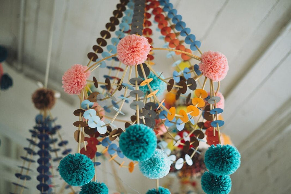 Pajaki chandelier made of colourful papers and tissue paper pom poms hanging from the ceiling