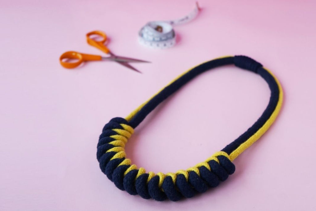 Rope knot necklace on a pink surface with scissors and measuring tape in the background