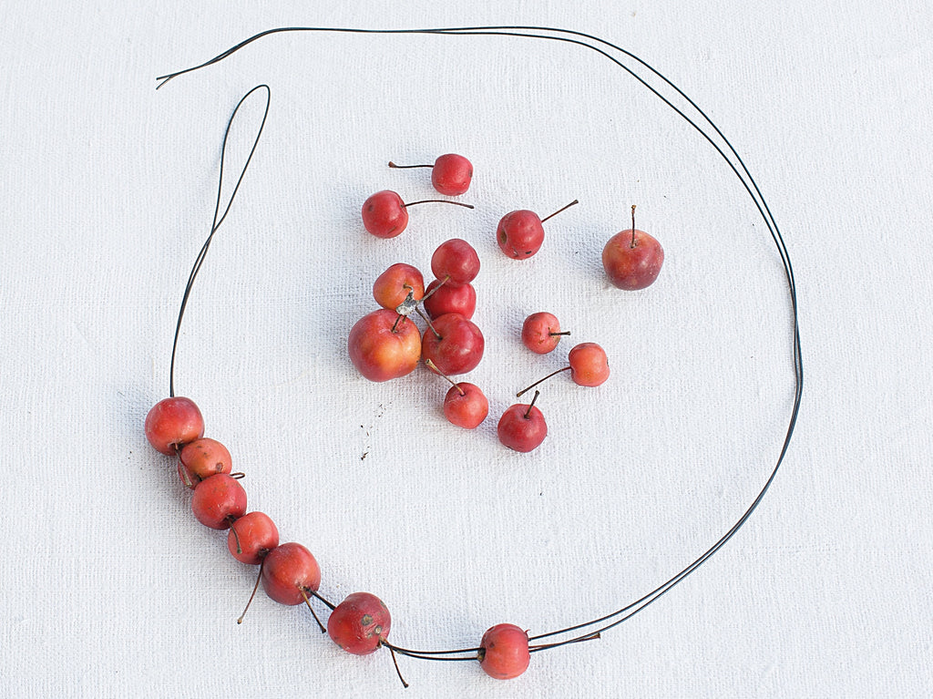 Threading crab apples on to florist wire