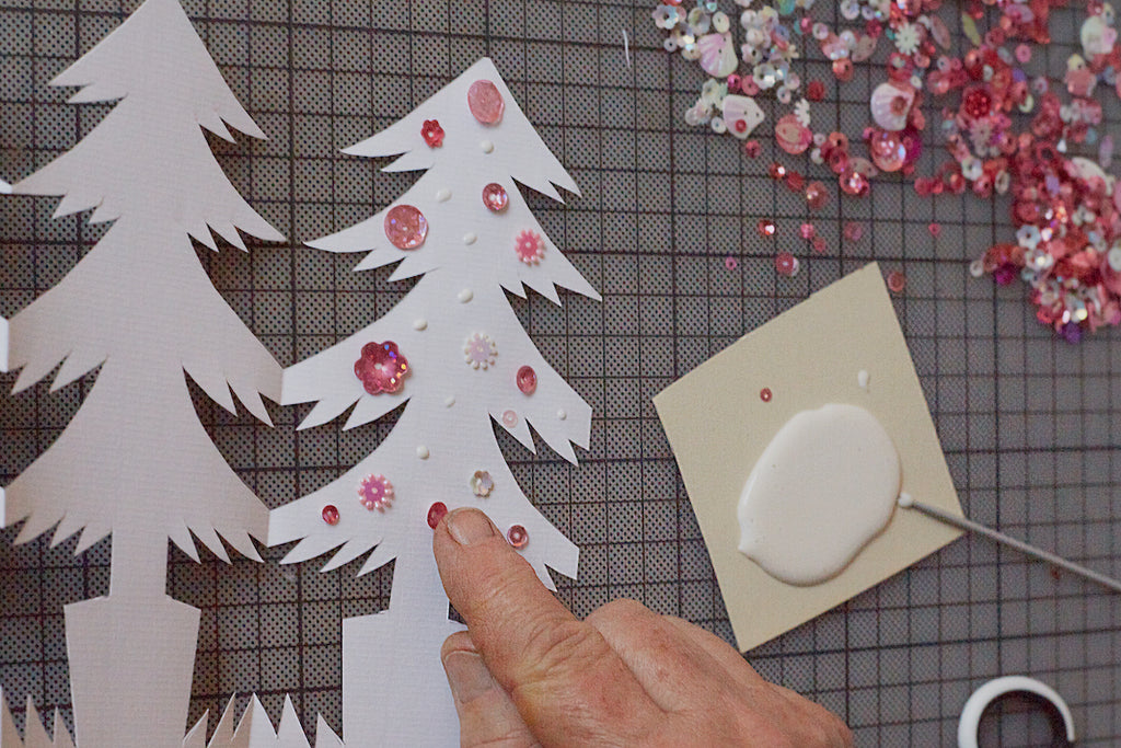 Add glue and colourful pink sequins to your paper garland.
