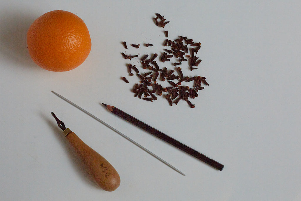 Orange, cloves, lino-cutting tool, cocktail sticks and a pencil are needed for making clove-spiked pomanders