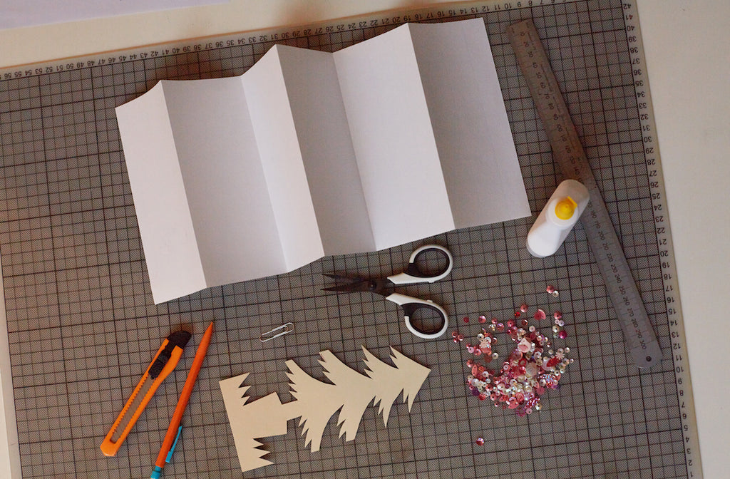 The materials needed to make a paper garland: paper, sequins, scissors, pencil