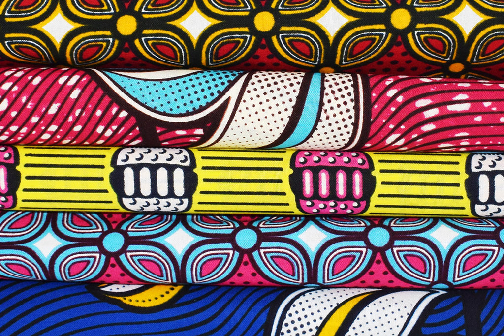 Assorted African wax print textiles, folded and lined on top of each other.