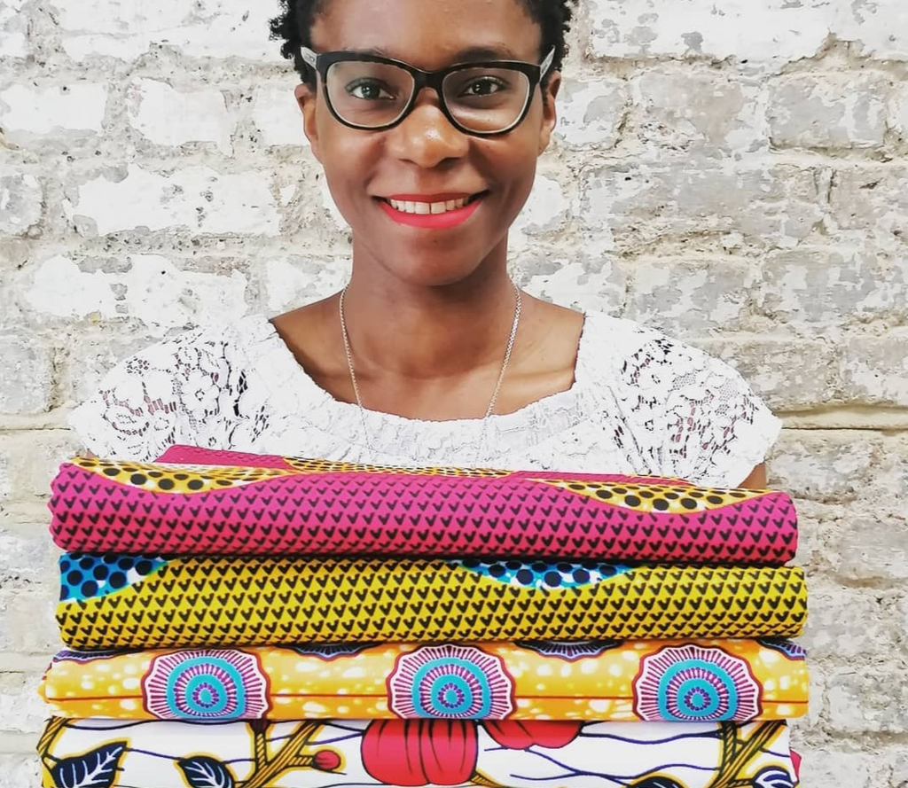Adaku Parker, a woman smiling and wearing glasses, holding a pile of folded colourful African Wax Print textiles.