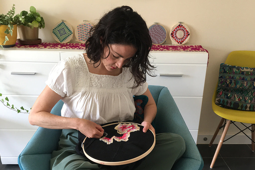 Alex sitting on a sofa chair concentrating on embroidering a floral design onto black fabric in an embroidery hoop.