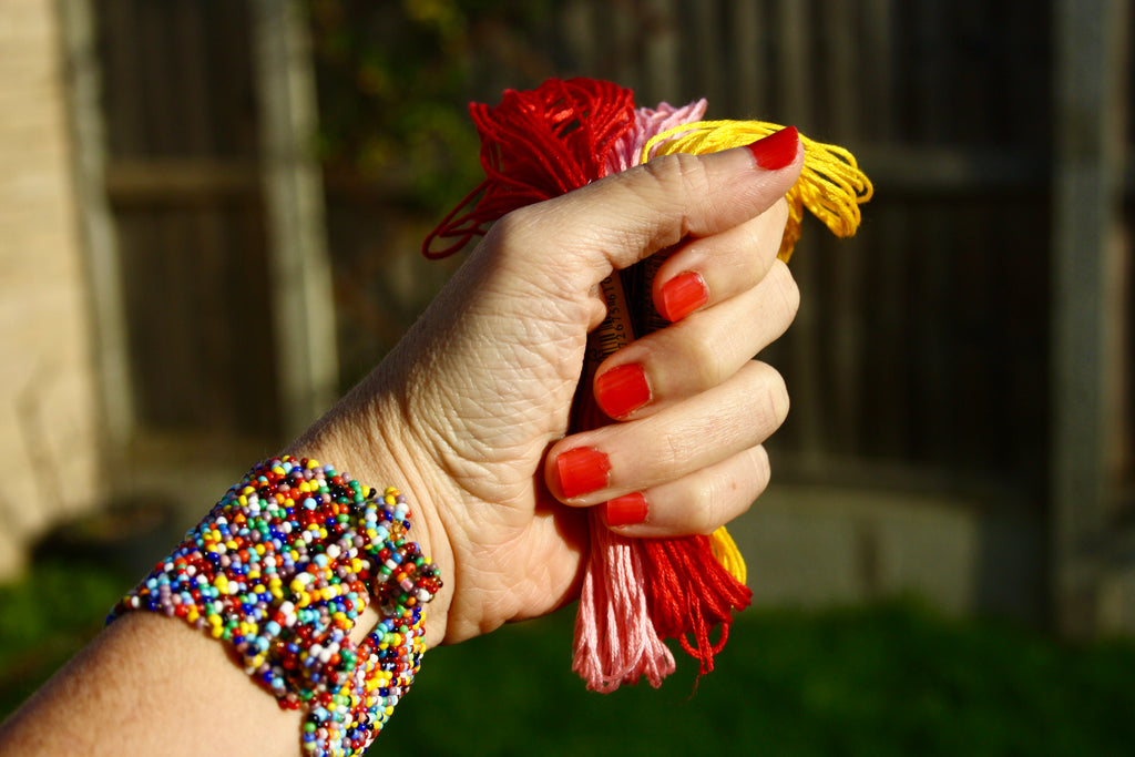 A hand grabbing several embroidery threads, wearing matching red nail polish with a thick beaded bracelet