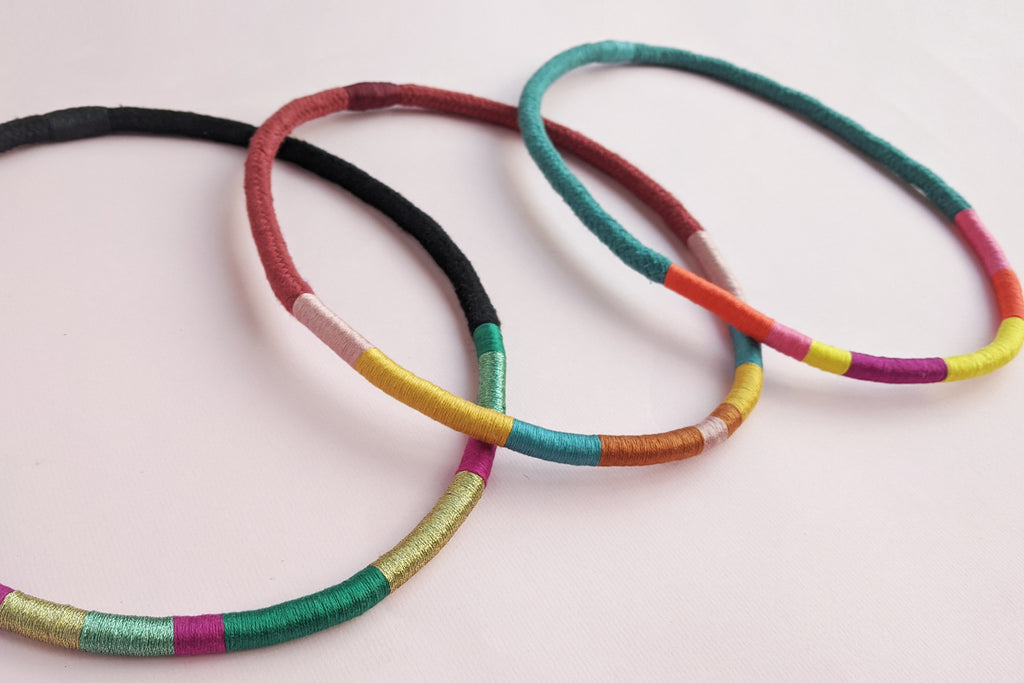 Three colourful wrapped rope necklaces lines up and overlapping each other