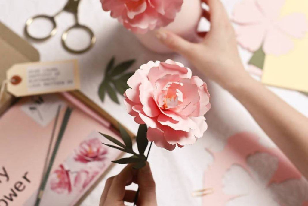 Pink paper peony held in one hand above a desk covered in scrap paper and papercraft tools.