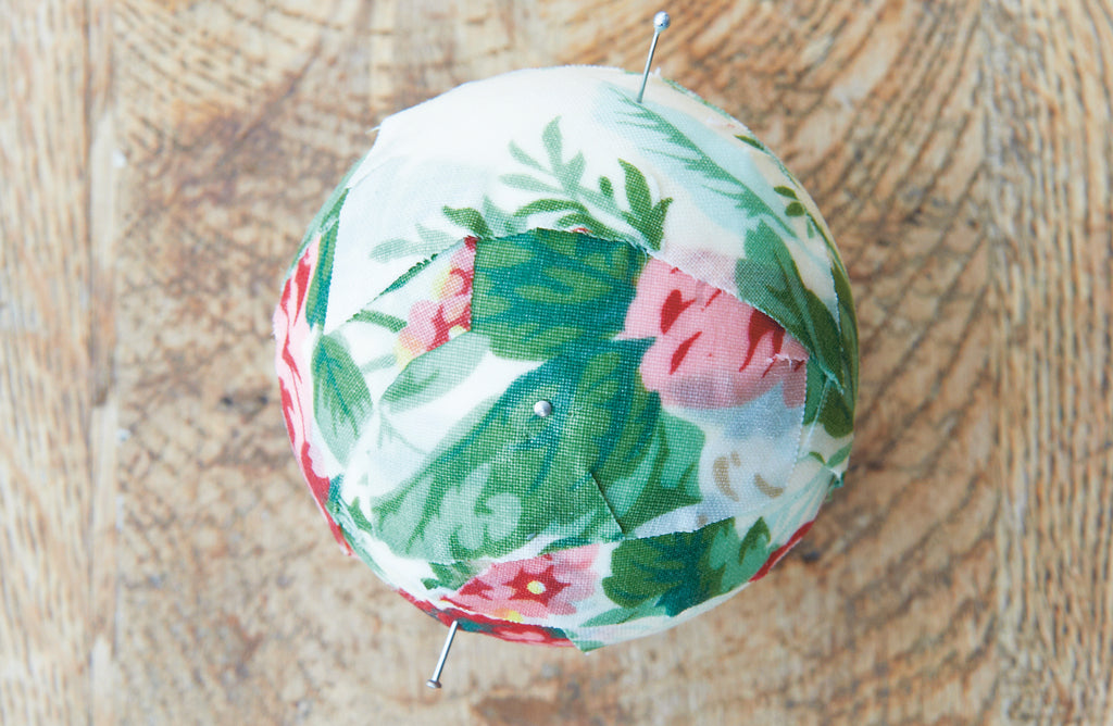 Christmas fabric bauble with dressmakers pins placed in