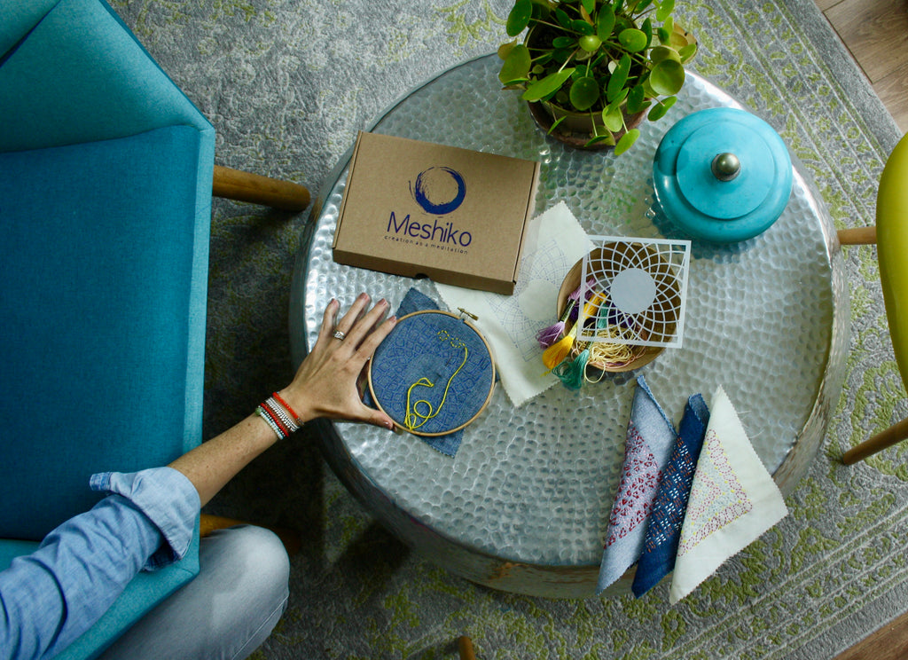 """A coffee table with a paper box labelled """"Meshiko"""", an embroidery hoop, fabric, embroidery threads, pattern, a plant and a blue jar."""