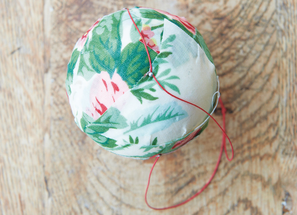 Add thread to the fabric Christmas bauble.
