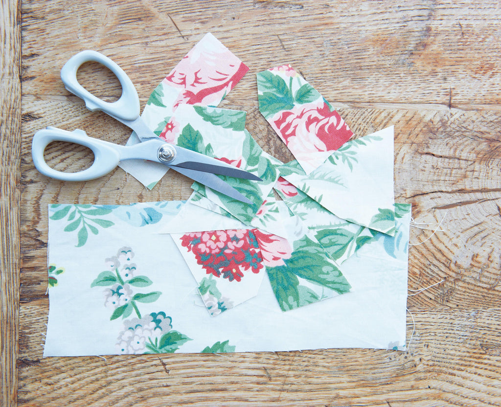 The floral fabric has been cut into small, irregular shapes with scissors.